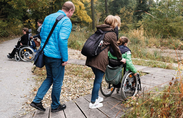 The picture shows wheelchair users passing a ramp in nature.