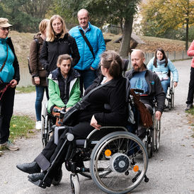 This picture shows members of the project team trying out what it feels like to experience nature in a wheelchair or with a cane for the blind. The guide in the wheelchair leads the group.