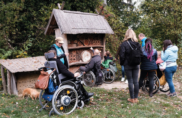 This picture shows members of the project team trying out what it feels like to experience nature in a wheelchair. Many of the people are in wheelchairs, all others are assistants and responsible for safety on the road.